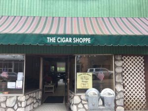 This pic is Outside the Cigar Shoppe in Ellwood City Pa.. With Green facing awning and thin green and large red stripes. stone wall on the bottom with glass windows above.
