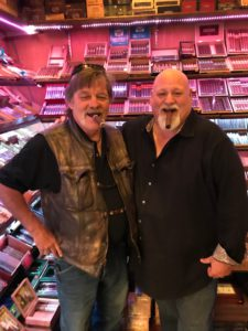 Steve Saka and me with our arms around each other, with cigars hanging out of our mouths and cigars on the shelves behind us