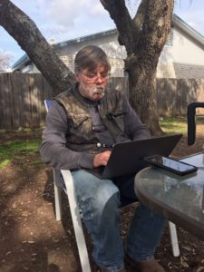 This is a picture of me under a tree sitting at a table with my laptop in my lap and a cigar hanging out of my mouth with smoke hard at work