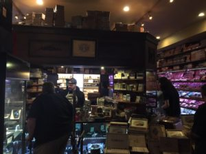Another pic in the humidor, looking straight back through the counter which  is four sided and has a roof with more cigars stacked on top and some people at the counter cashing out.