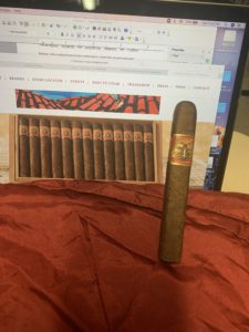 pic of wise man cigar that. I am reviewing on a red scarf in front of my computer screen showing a box of them